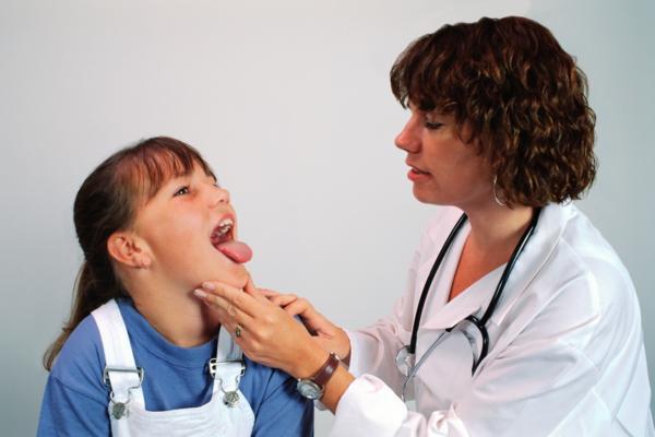 девочка показывает горло врачу